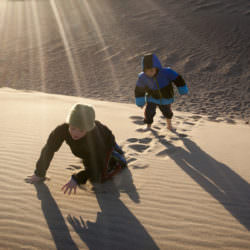 Two boys climb up sand dunes at the Sand Dunes National Park.