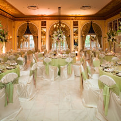 Wedding reception with white table settings with green accent.