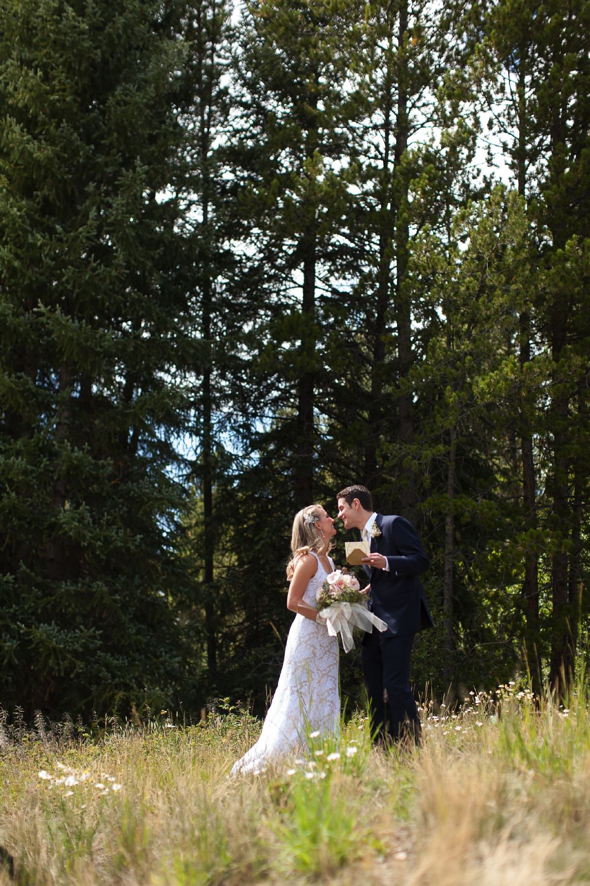 Bride and groom kiss in a field surrounded by pine trees.