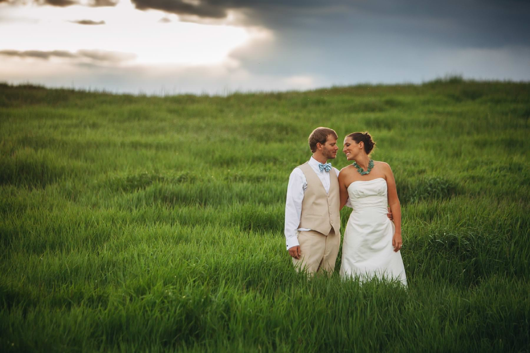 Couple in tall grass share a kiss at Catamount Lake House