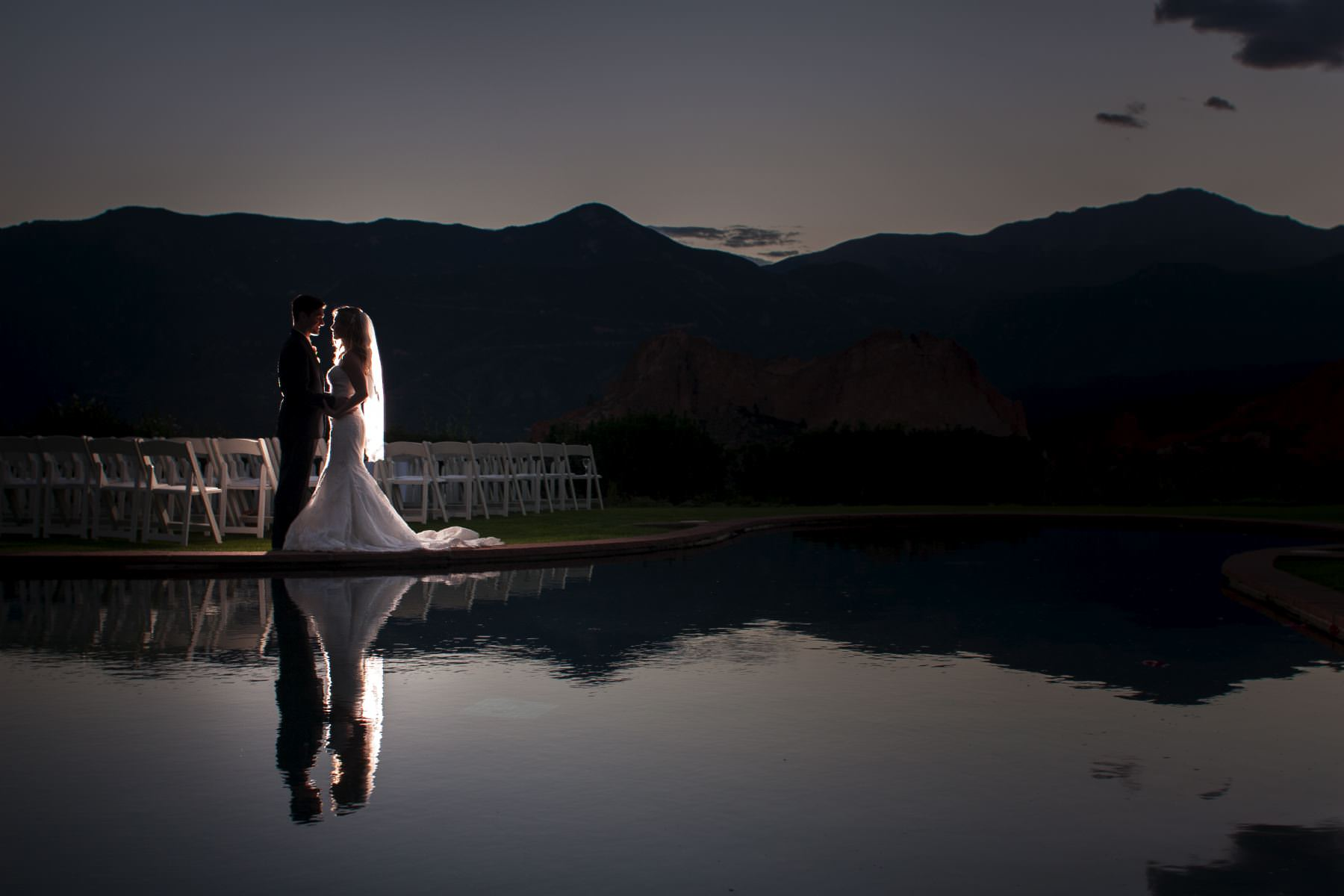 Bride and groom at sunset in front of reflection pool at the Garden of the Gods Club.