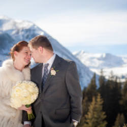 Bride with white rose bouquet and groom share a moment at the top of Hoosier Pass.