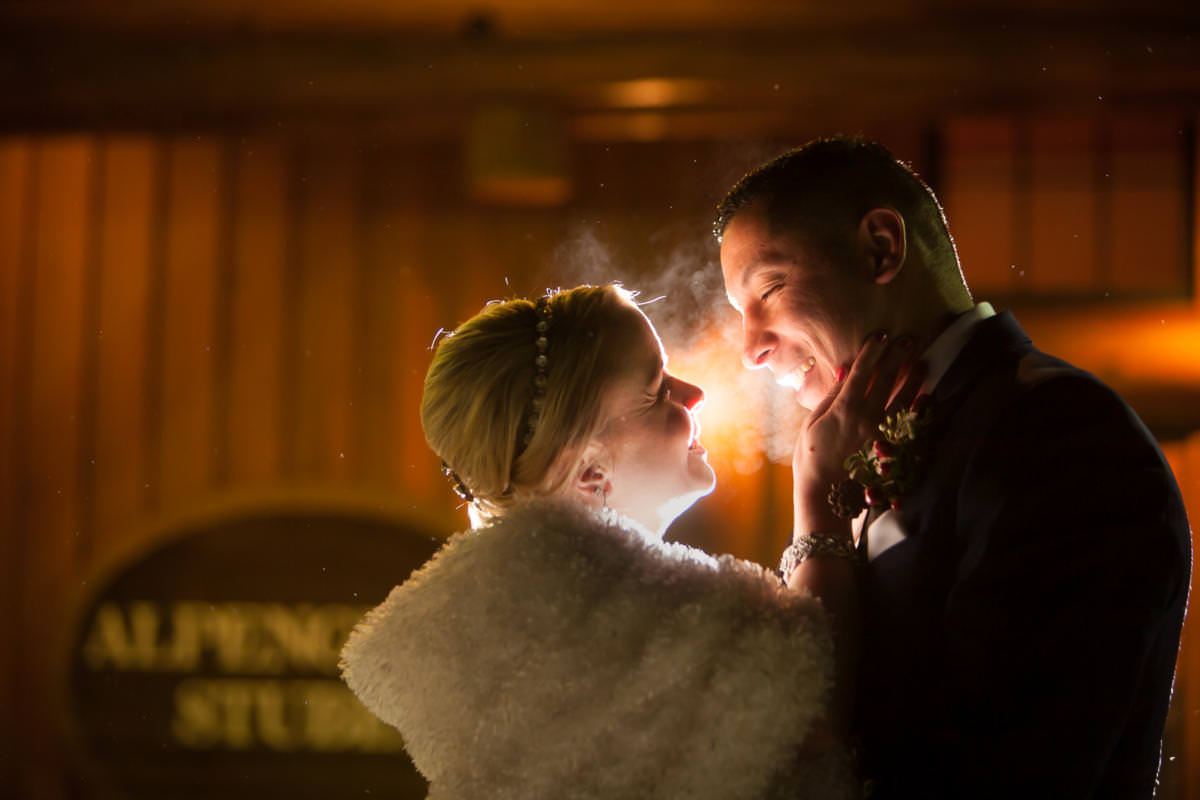 Bride and groom embrace in the snow at night outside during their Alpenglow Stube Wedding Celebration.