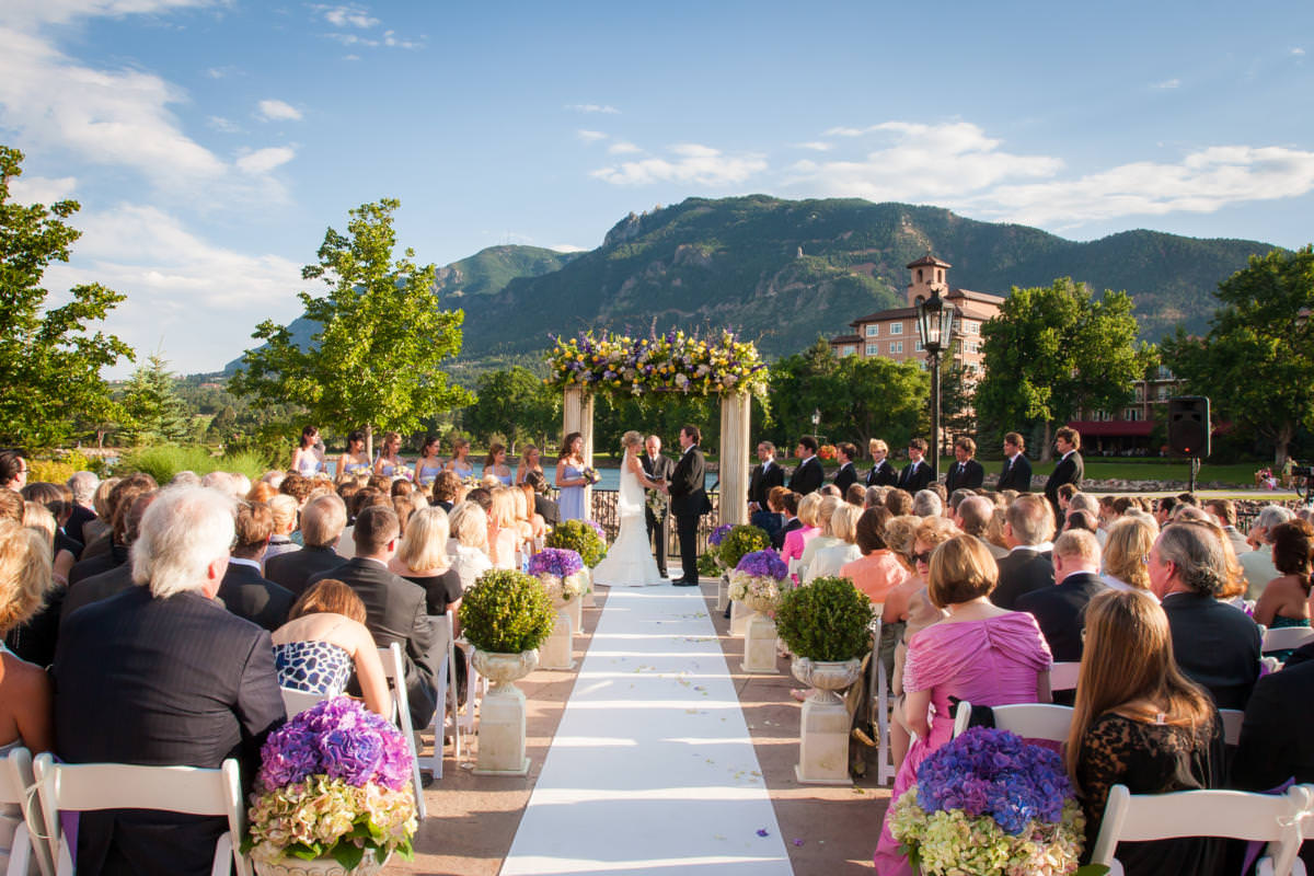 Wedding ceremony with bride and groom under wedding arch at The Broadmoor's Lakeside Terrace.