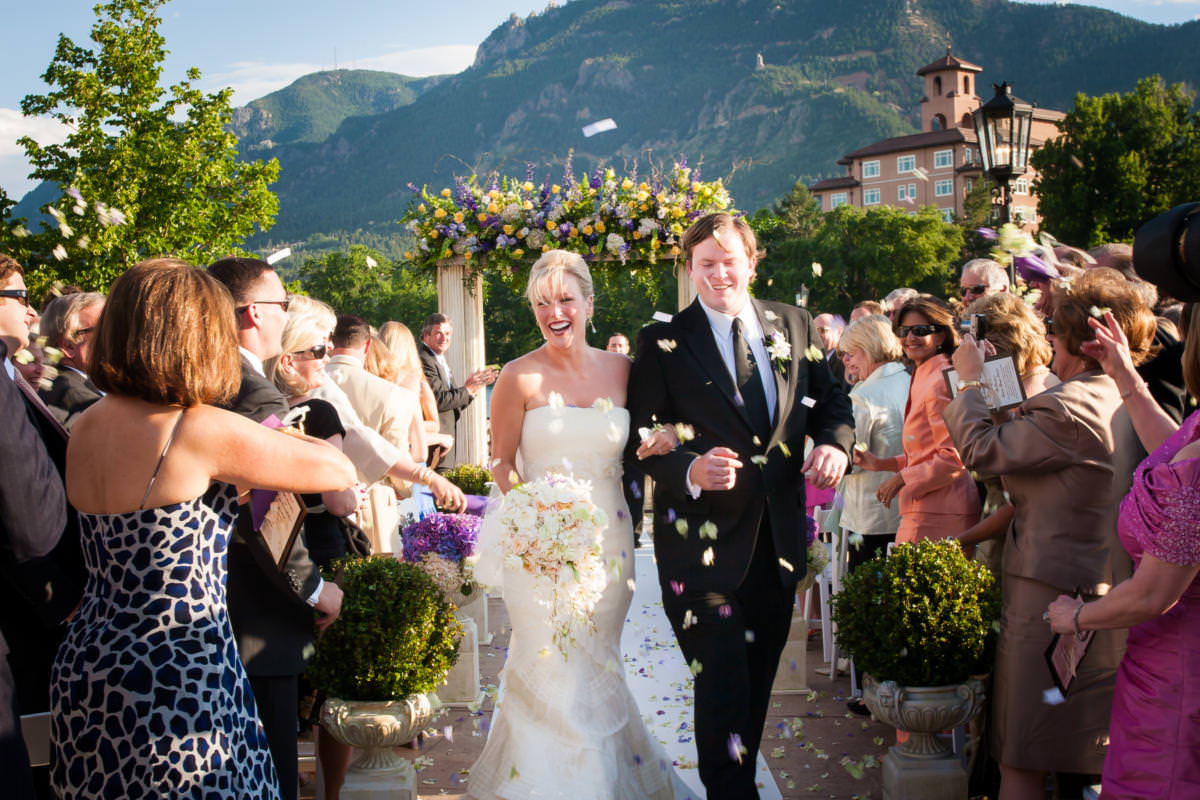 Bride and groom exit their wedding ceremony under tossed flower petals at The Broadmoor's Lakeside Terrace.