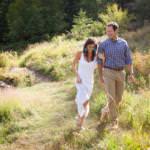 Couple walking arm-in-arm through a field.