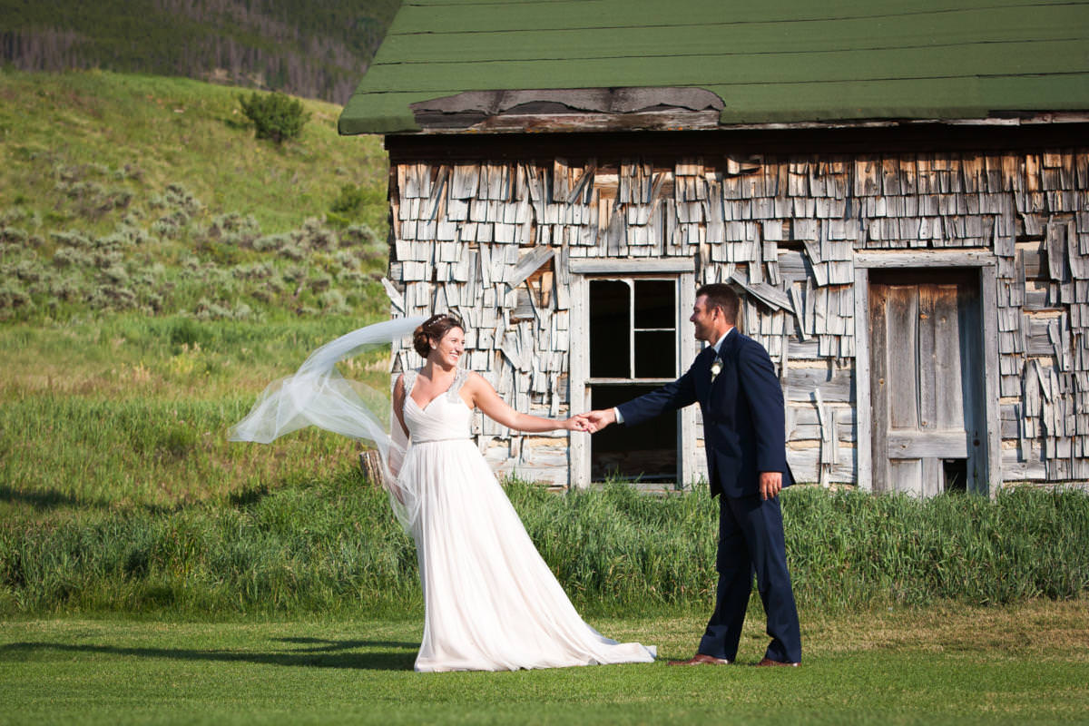 Bride and groom hold hands and walk together in front of old building with shingles and green roof at Keystone Ranch.