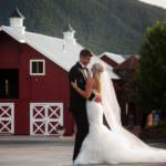 Bride and groom embrace at sunset outside red and white barn at Crooked Willow Farms.