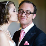 Bride kisses groom on the cheek.