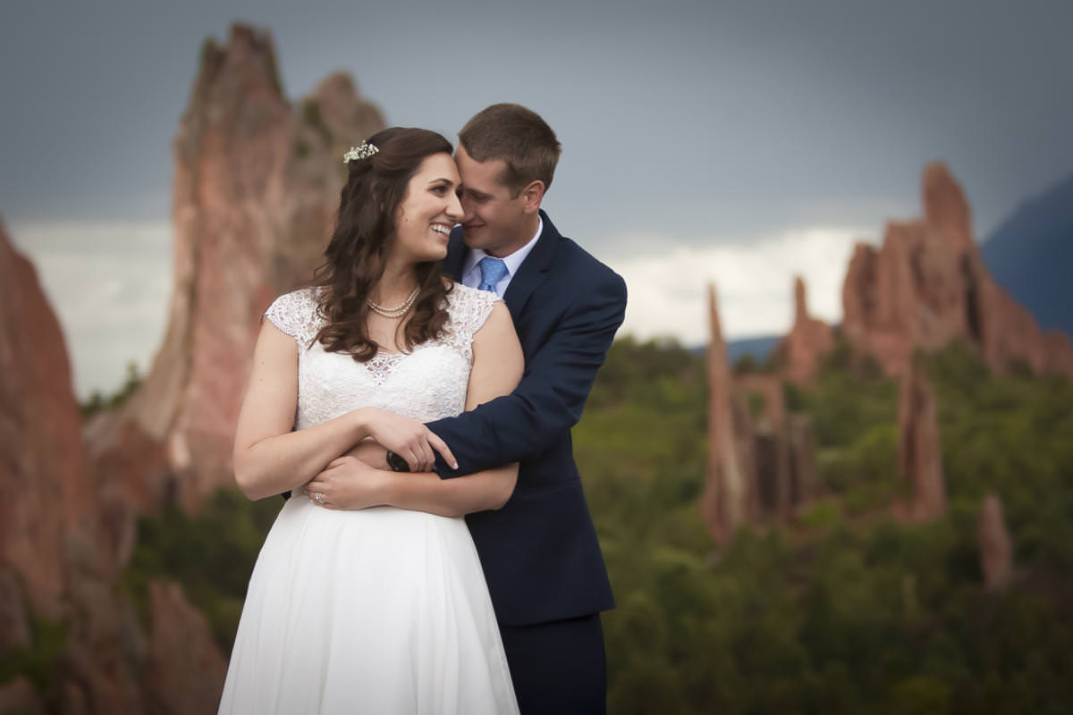Alexandra and Christopher share an embrace at Garden of the Gods park after their Hillside Gardens wedding celebration.