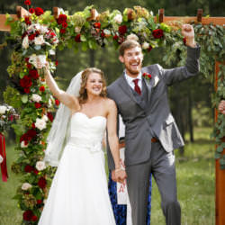 Wedding couple raise their hands in celebration at the end of their wedding ceremony at La Foret Conference and Retreat Center.