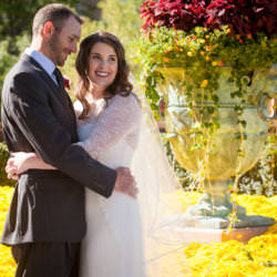 Bride and groom hold each other in front of yellow and red flowers.