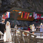 Bride and groom walk over the bridge at Seven Falls.