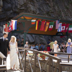 Bride and groom walk over the bridge at Seven Falls.