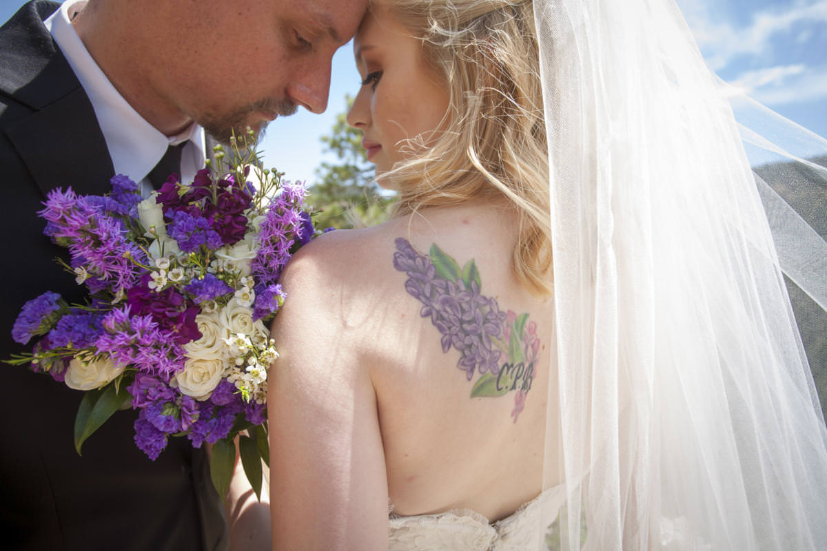 Bride and groom embrace with purple bouquet and tattoo.