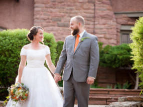 Bride and groom hold hands outside the entrance of SunMountain Center in Manitou Springs, Colorado.