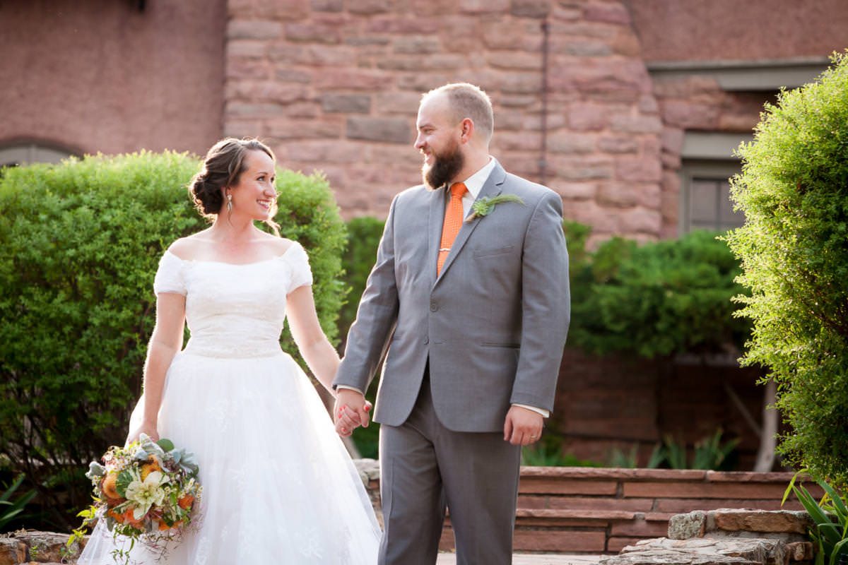 Darcie and Ryan hold hands during their SunMountain Center wedding.