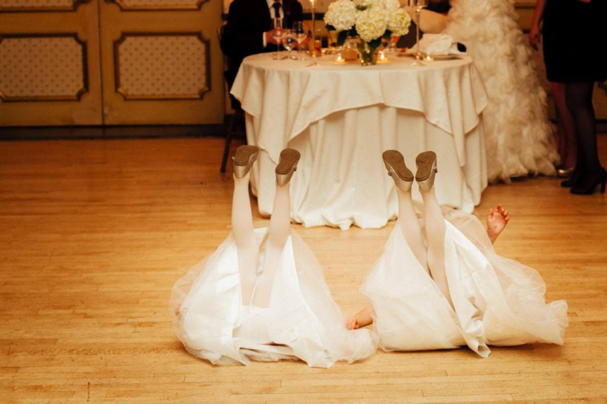 Two flower girls with feet raised on the dance floor.