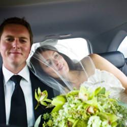 Bride holding champagne flute leans on the shoulder of groom inside a car.