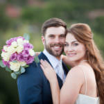 Bride and groom smiling with white and purple wedding bouquet.