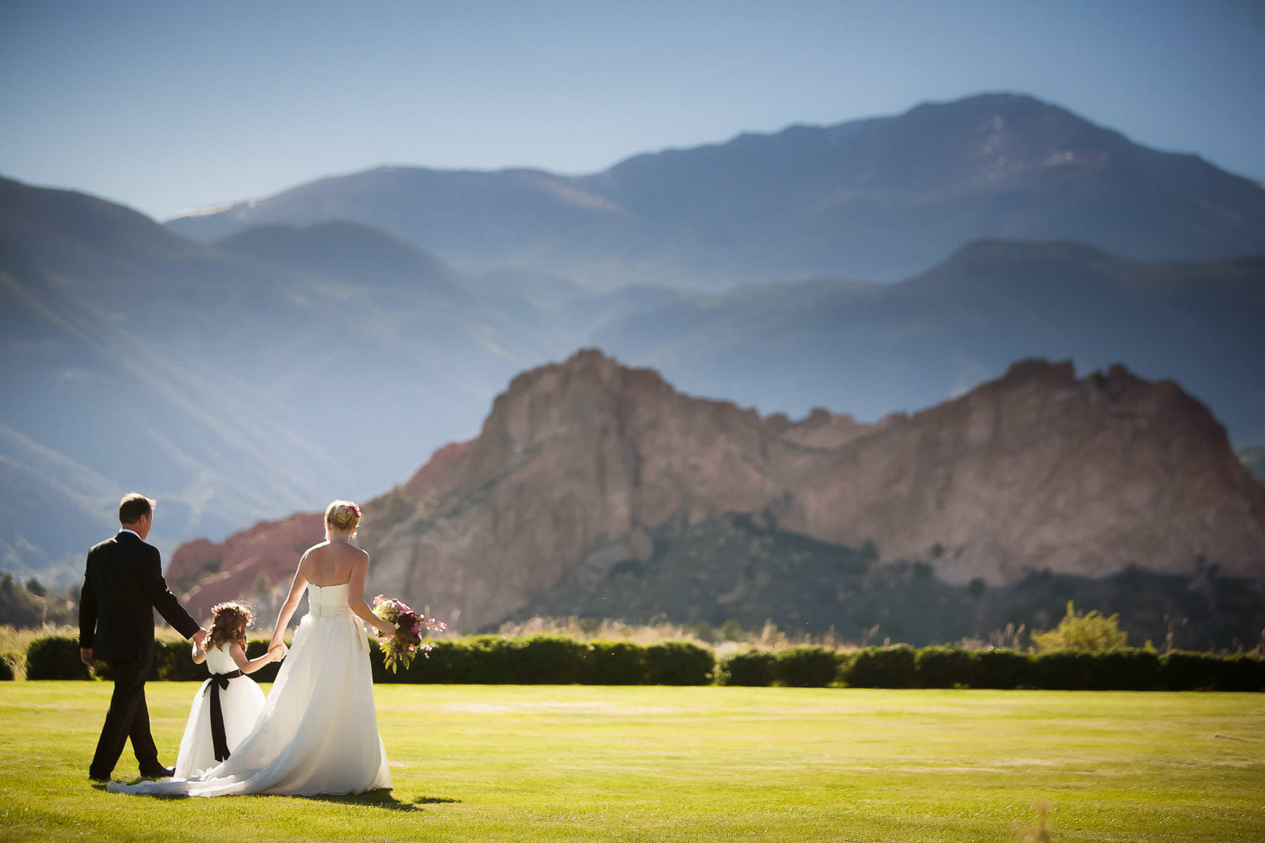 Bride, groom, flower girl walk on the south lawn of the Garden of the Gods Club with Pikes Peak.