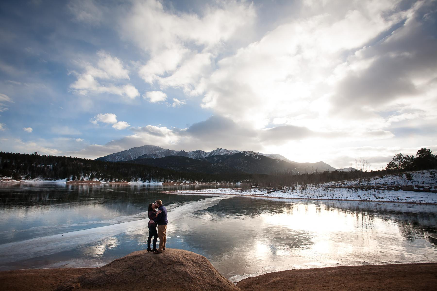 Couple kissing with lake and Pikes Peak in snow.