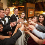 Bride and groom toasting with friends at the Craftwood Inn.