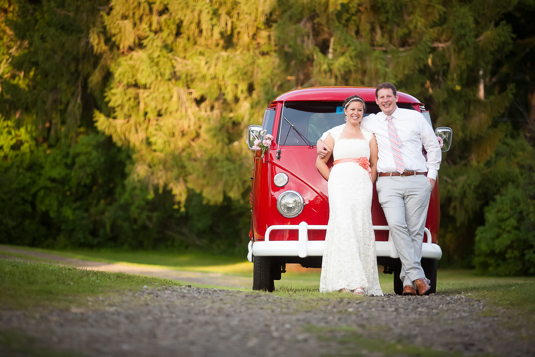 Bride and groom stand in front of an antique volkswagon bus,