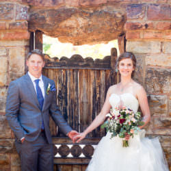 Bride and groom hold hands in front of wooden door leading the Carriage House at the Glen Eyrie Castle.