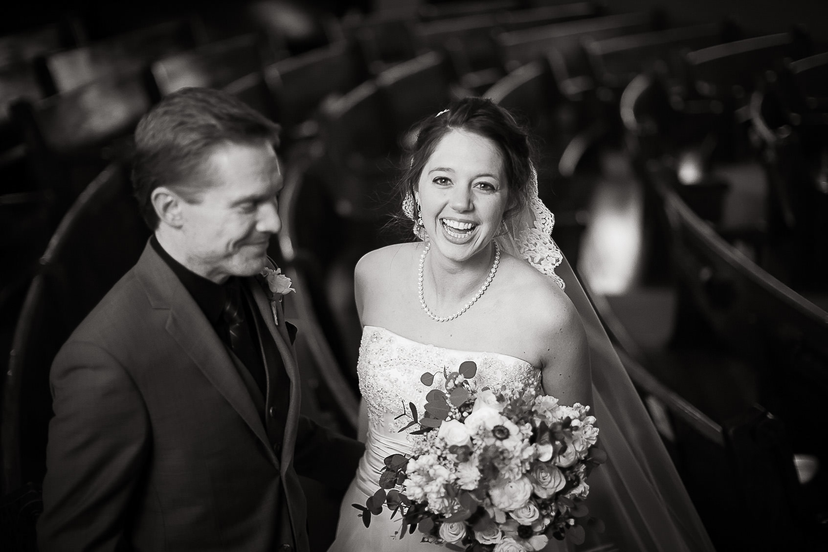 Black and white of bride and groom laughing together in the sanctuary of Boulder Street Church.