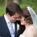 Bride and groom with heads together in a repose after wedding ceremony.