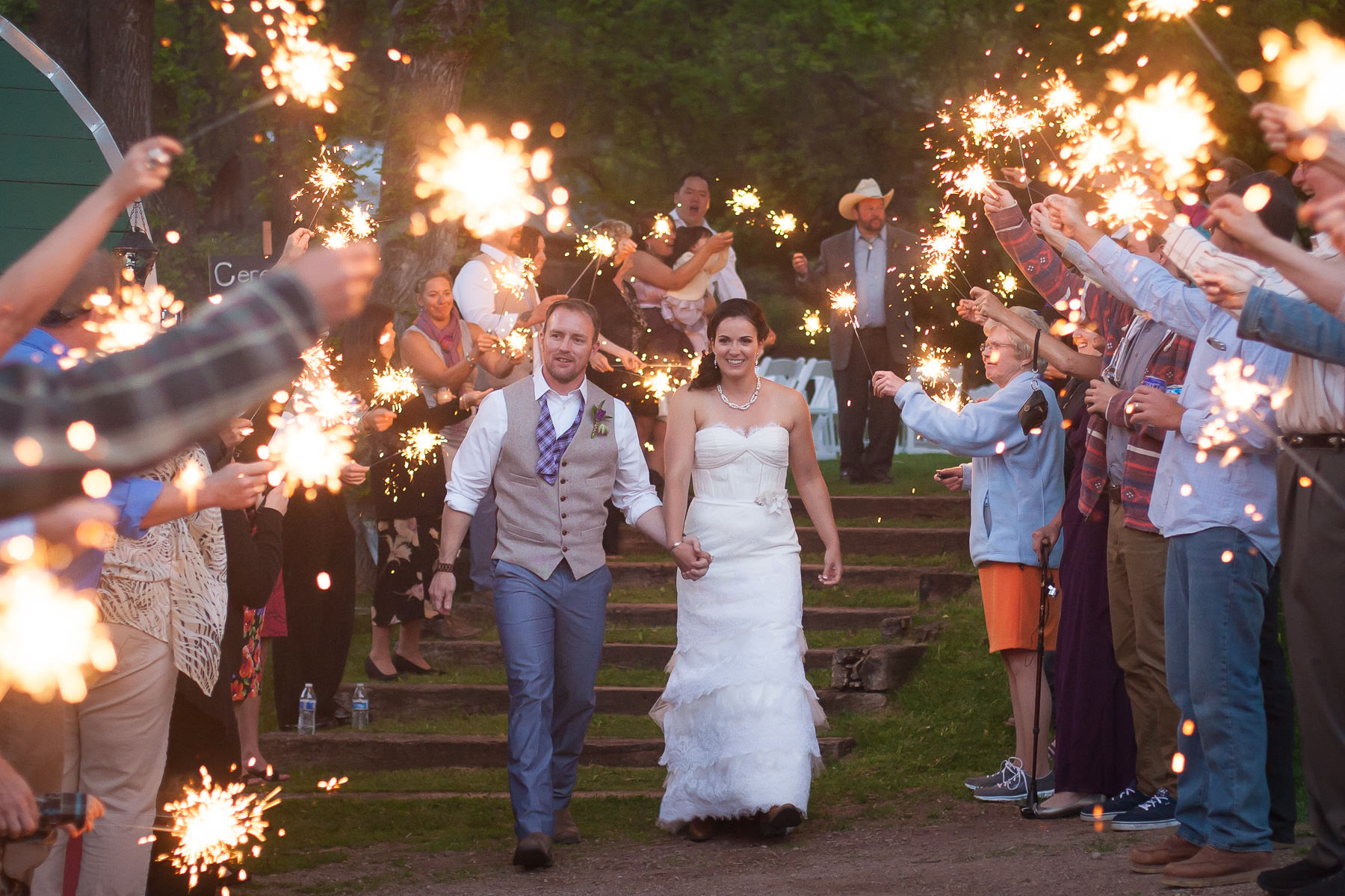 Bride and groom hold hands and walk down an aisle of sparklers.
