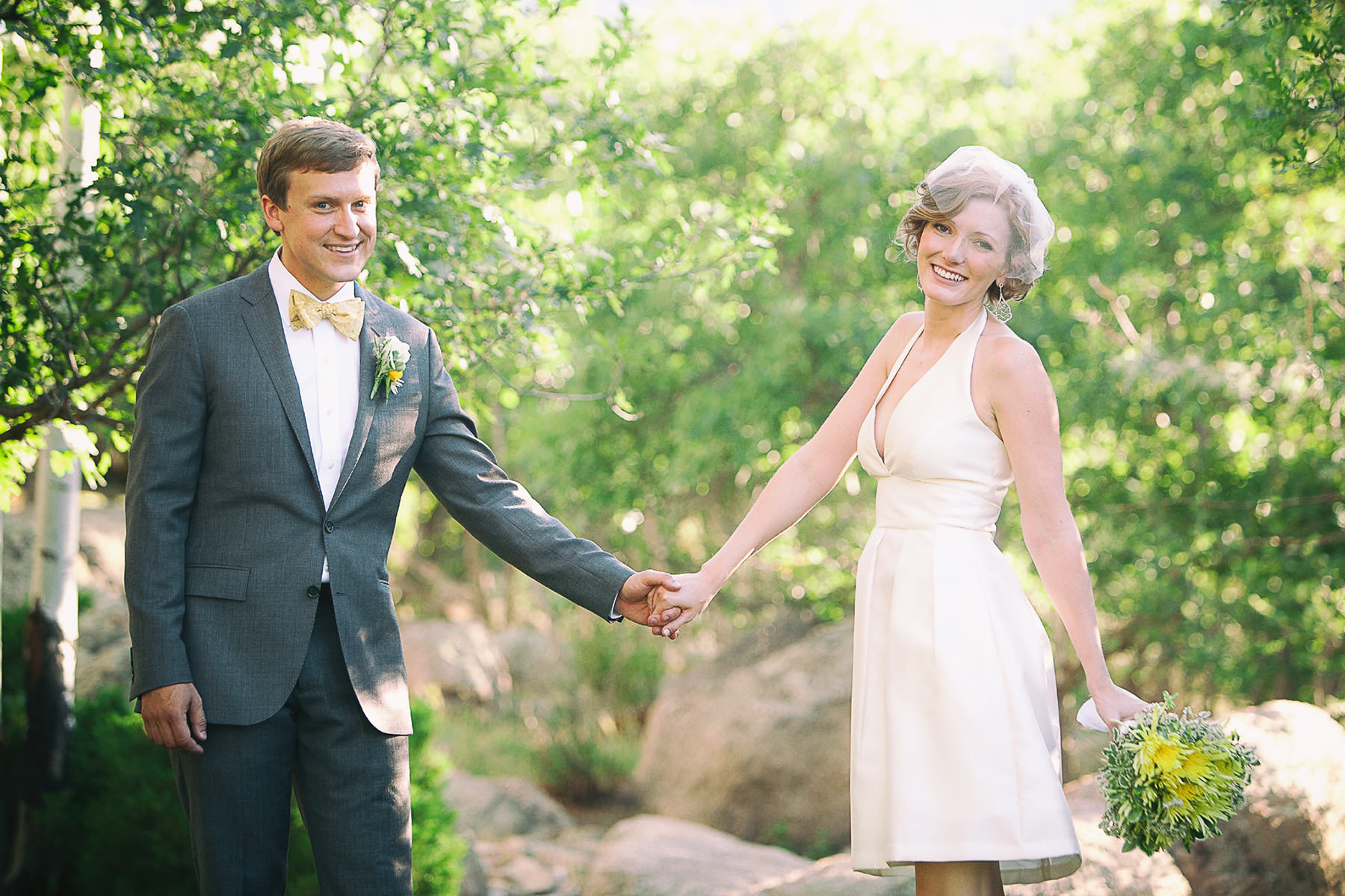 Bride and groom hold hands in a sun-drenched grove of scrub oak.