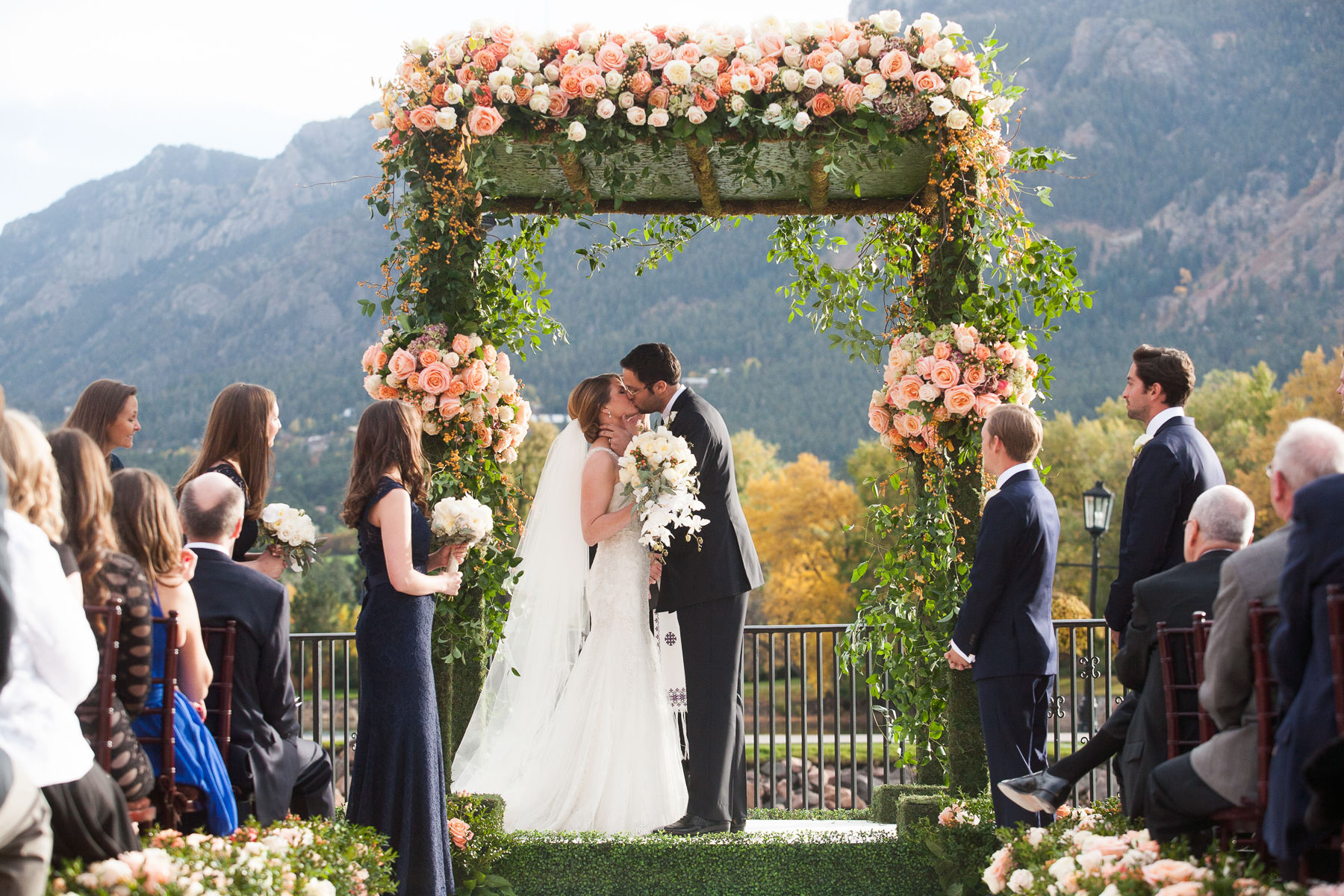 Bride and groom kiss at the altar at Lakeside Terrace at The Broadmoor