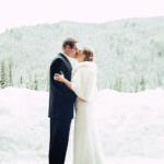 Bride and groom kiss in the snow at Ski Tip Lodge
