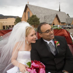 Bride and groom ride in horse carriage in front of St. Paul Catholic Church