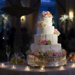 Tiered fondant wedding cake with red, orange and pink roses