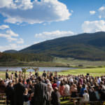 Outdoor wedding ceremony at Keystone Ranch with lake, mountains and blue sku