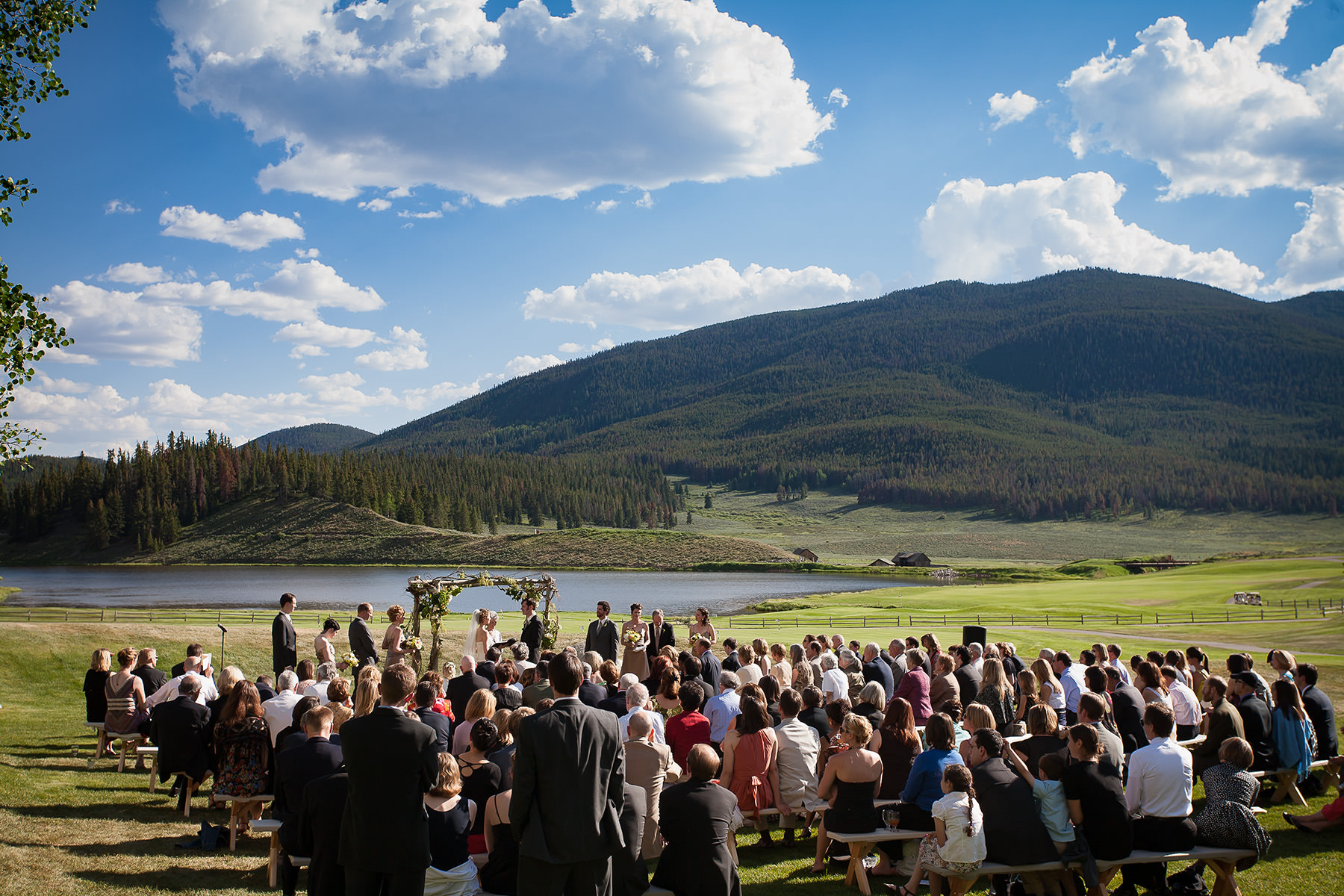 Outdoor Wedding Ceremony At Keystone Ranch With Lake Mountains And Blue Sku