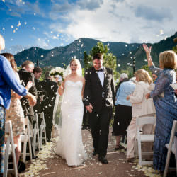 Bride and groom exit their outdoor wedding ceremony underneath white rose petals tossed into the air at The Broadmoor's Cheyenne Lodge.