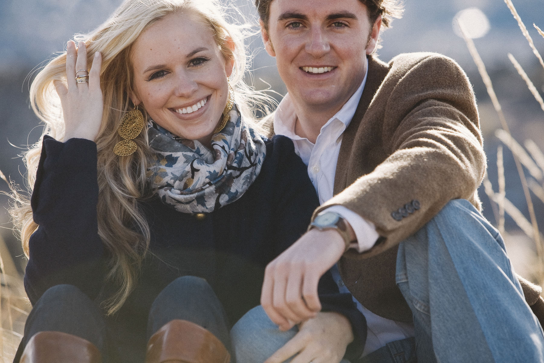 Engaged couple in black coat, camel hair coat and jeans sit in a sun-drenched field.