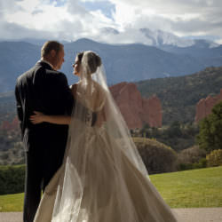 Bride and groom embrace in front of Pikes Peak and Garden of the Gods Club.