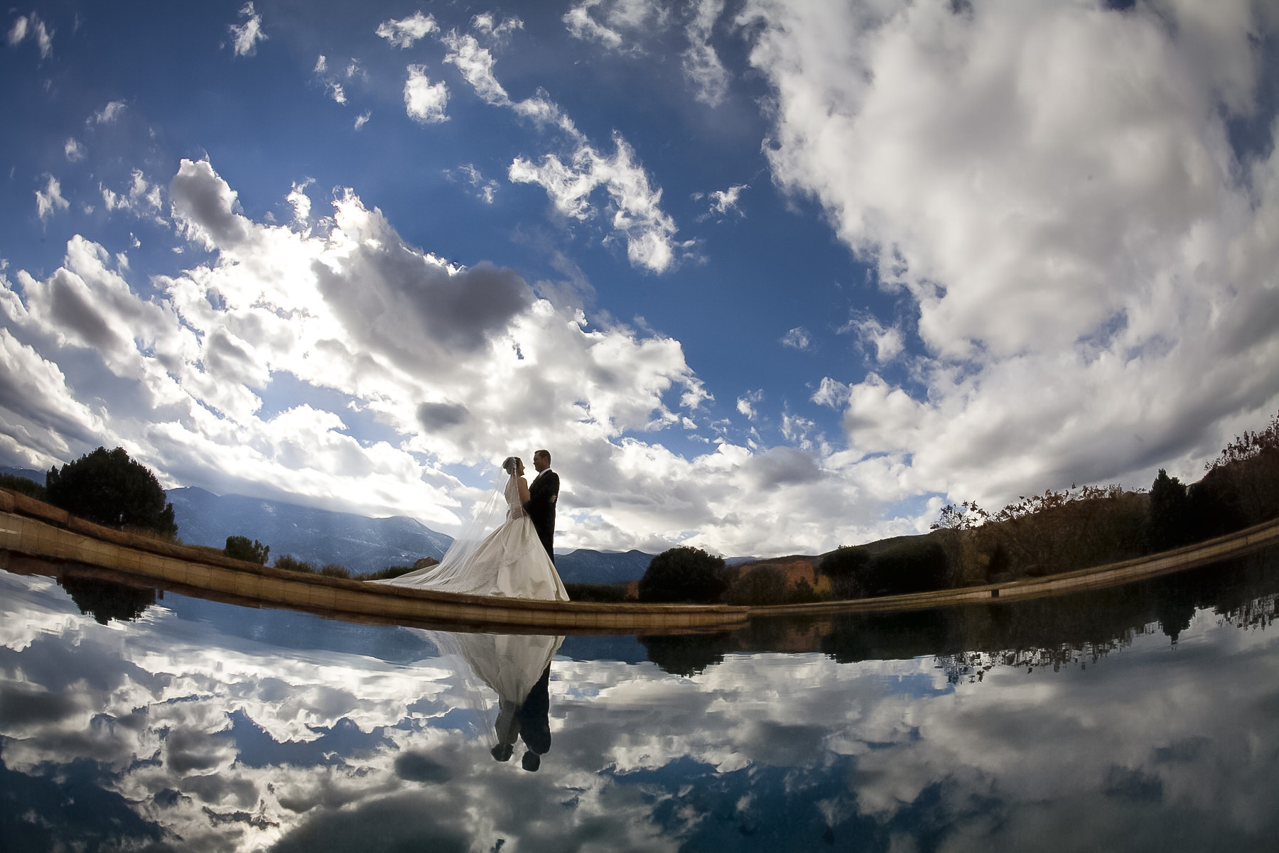 Bride and groom together in front of reflection pool with blue sky and clouds.