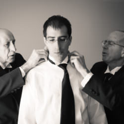 Black and white of two men tying groom's tie.
