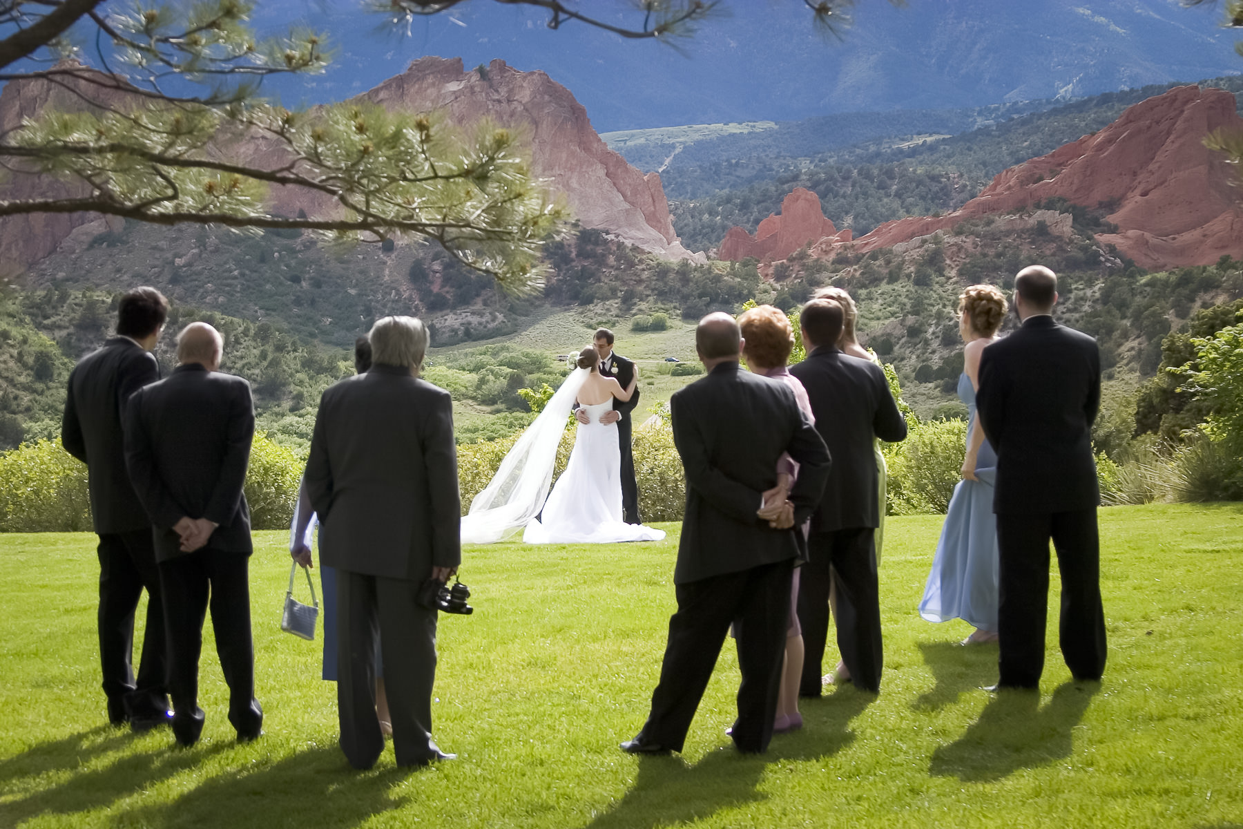 Bride and groom on the lawn of the Garden of the Gods Club being watched by wedding guests.