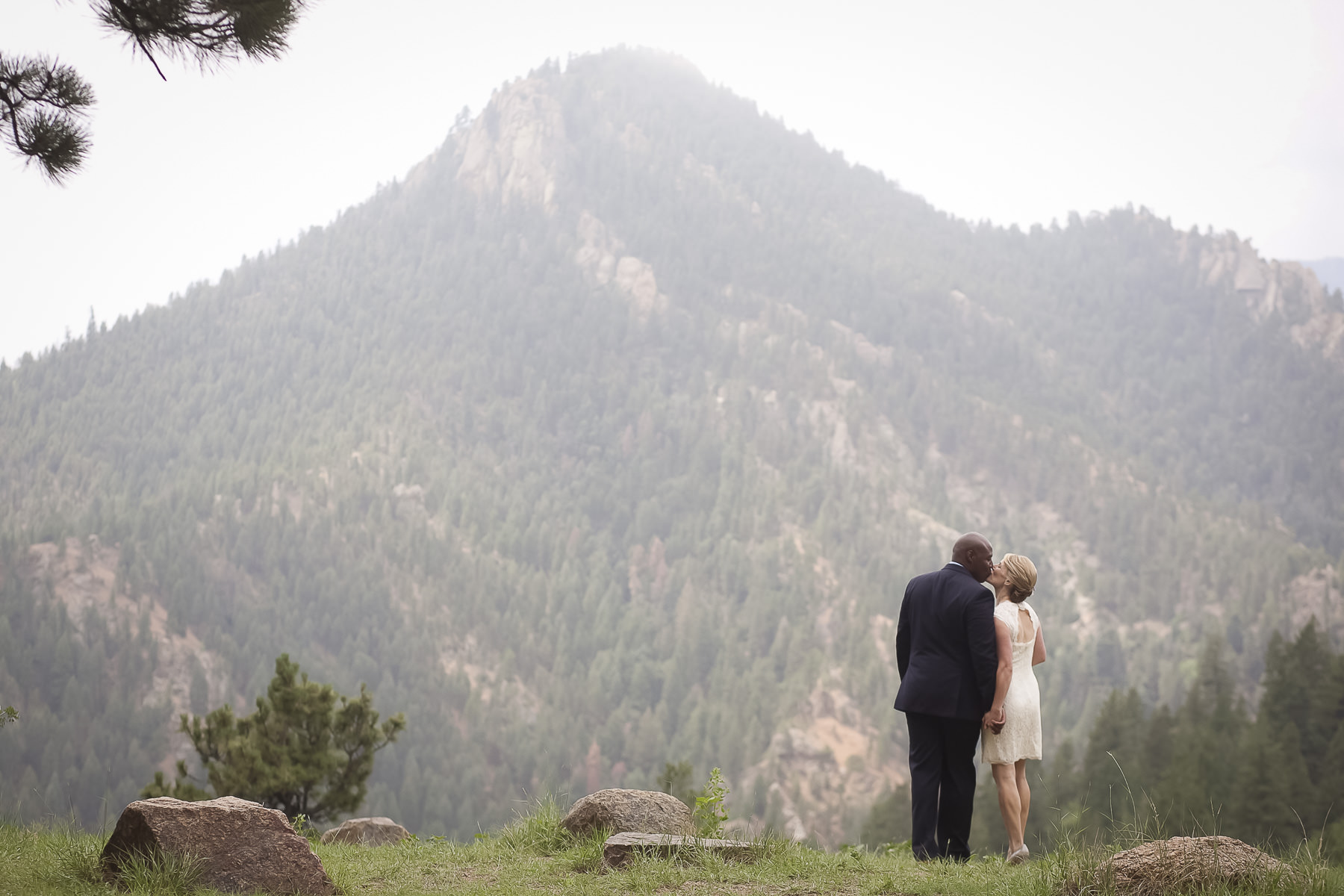 Bride and groom kiss in field overlooking Cheyenne Canon.