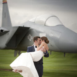 Groom in Air Force mess dress lifts bride and kisses her in front of a military jet on display at the Air Force Academy.