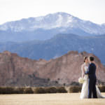 Bride and groom kiss in front of the Garden of the Gods park and snow-capped Pikes Peak.
