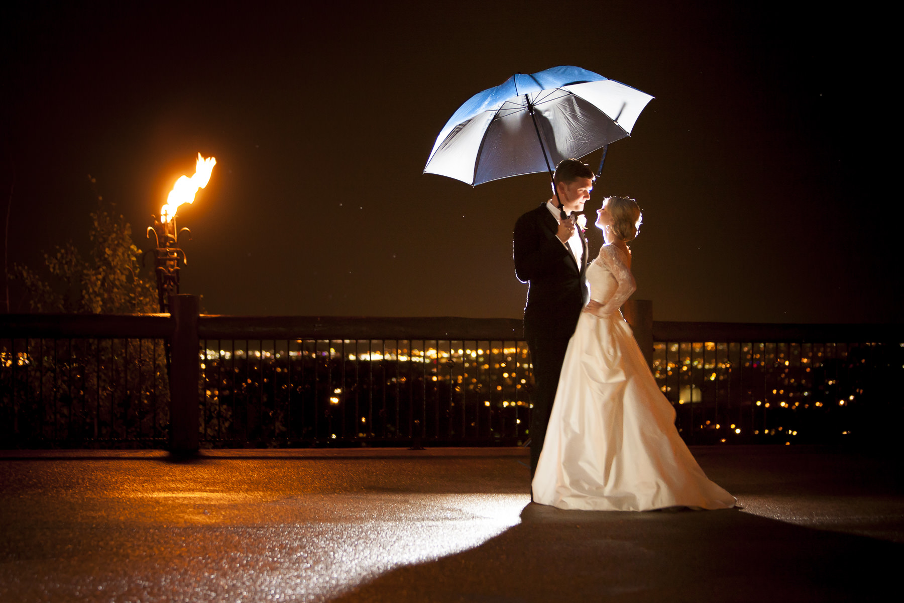 Chapel of Our Saviour Wedding Photographer: Night shot of bride and groom with umbrella, torch and city lights Cheyenne Lodge.