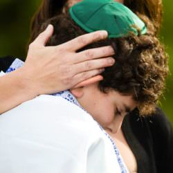 Boy wearing yamaka and tallit during Bar Mitzvah ceremony at Cheyenne Lodge.